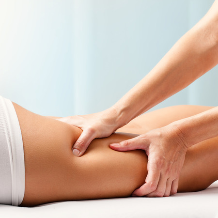 pressure massage: Macro close up of Osteopathic hamstring massage.Therapist applying pressure with hands on back go female leg. Stock Photo