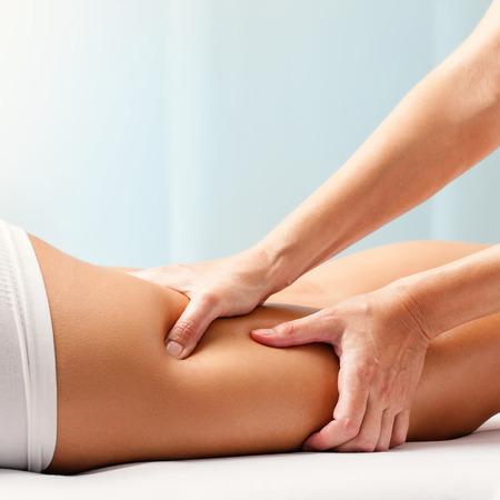 leg massage: Macro close up of Osteopathic hamstring massage.Therapist applying pressure with hands on back go female leg. Stock Photo