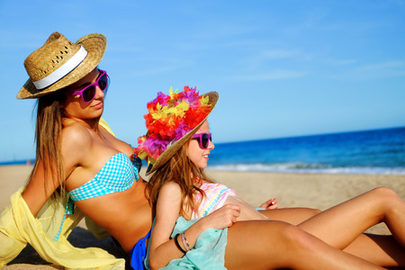 looking aside: Close up portrait of two suntanned young girls in swimwear sitting together on beach. Women wearing straw hats and fun purple sunglasses looking aside into distance.