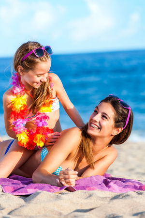 Close up portrait of two happy young women on summer holidays having fun together on beach.