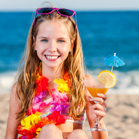 teen beach: Close up portrait of attractive little preteen girl on beach holding fruit cocktail.