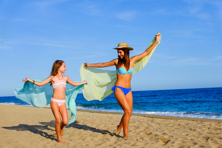 child swimsuit: Action portrait of Joyful young girls running with color foulards. Young mother with daughter on holiday at beach. Stock Photo