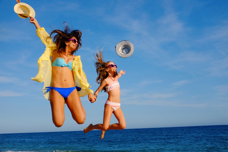 teen girls: Action portrait of young mother with daughter  jumping together on beach. Laughing girls in swimwear throwing hats in air.