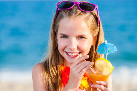 Close up head portrait of attractive little girl drinking fruit cocktail on beach.