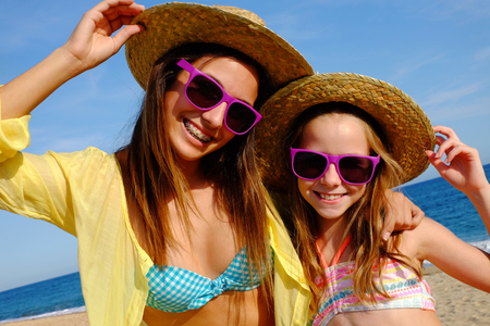 summer holiday bikini: Close up outdoor portrait of attractive young mother and daughter on beach wearing straw hats and fun purple sunglasses.