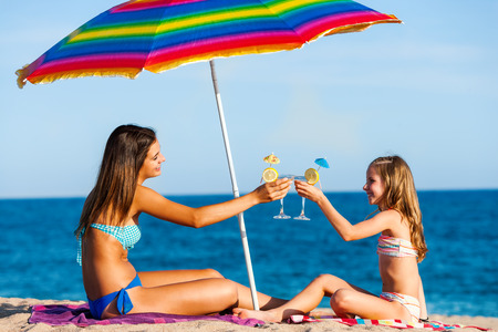 anniversary beach: Portrait of two young girls on summer holiday. Young women sitting under colorful umbrella on beach drinking fruit cocktails.