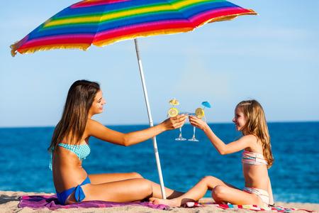 cocteles de frutas: Retrato de dos chicas jóvenes en las vacaciones de verano. Las mujeres jóvenes sentados bajo el paraguas colorido en la playa bebiendo cócteles de frutas. Foto de archivo