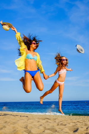 summer wear: Close up action portrait of Young girls in swimwear jumping on beach. Two attractive happy women in bikini and sunglasses throwing hats in air. Stock Photo