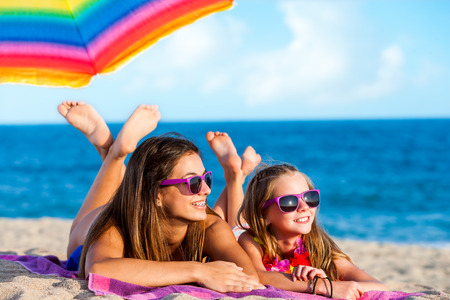 parent and child: Close up portrait of two young girls laying together on beach. Young women wearing fun purple eyewear.