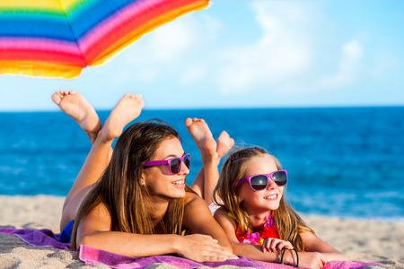 Close-up portret van twee jonge meisjes die samen op het strand. Jonge vrouwen het dragen van plezier paarse brillen.