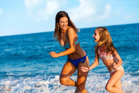 dadã  daughter: Retrato de Acción de dos chicas jóvenes que tienen buen tiempo en la playa. Muchachas que se ejecutan y salpicaduras de agua.