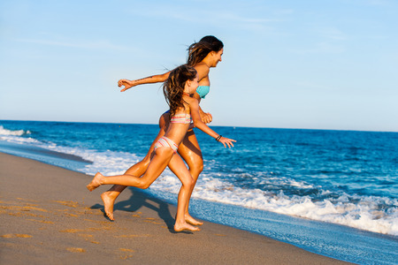 sunny beach: Action portrait of Young girls on holiday. Two women running towards blue sea.