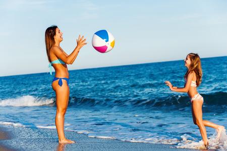 Close up in voller Länge Portrait von zwei jungen Mädchen, die mit aufblasbaren Ball am Strand. Standard-Bild - 46292907