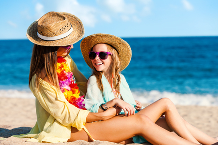 child in bikini: Close up portrait of young mother and daughter on summer holidays. Two young women in swimwear with straw hats and fun purple sunglasses. Stock Photo