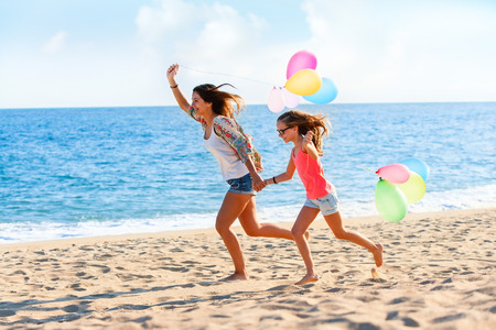 Action portrait of Young girls running with colorful balloons on beach.