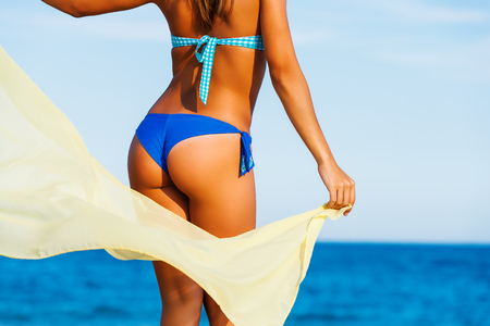 beautiful nude woman: Close up rear view of Attractive female suntanned body on beach. Young woman in blue bikini playing with yellow scarf in wind.