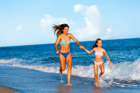 kids playing beach: Action portrait of two young happy women running and slashing water  along beach.