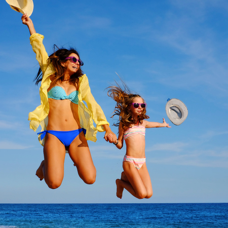 bikini wear: Close up action portrait of young girls on holiday jumping on beach. Two attractive happy women in bikini and sunglasses throwing hats in air.