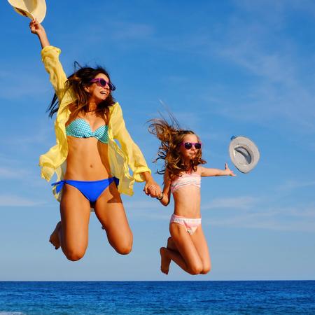 madre e hija adolescente: Close up retrato de acción de las niñas en el salto de vacaciones en la playa. Dos mujeres felices atractivas en bikini y gafas de sol que lanzan los sombreros en el aire.