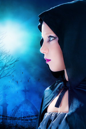 Close up portrait of attractive young mysterious gothic girl wearing black hood.Graveyard with full moon in background. photo
