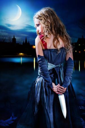 satan: Close up retrato misteriosa chica gótica que sostiene un cuchillo detrás de la espalda. Chica de pie con el cuchillo grande detrás de la espalda en la oscuridad. Paisaje urbano medieval en el fondo con la reflexión sobre el agua oscura.