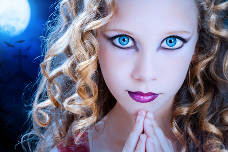 Extreme close up facial portrait of young Girl with big blue eyes. Beauty cosmetic make up on pre teen with graveyard at full moon in background. photo