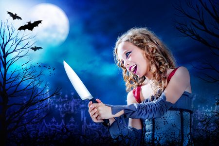Close up horror portrait of Young female vampire holding big knife at dusk.Full moon and flaying bats over graveyard in Background. photo