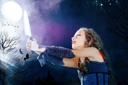 Close up portrait of young female vampire holding big knife. Castle towers and crows flaying in full moon background. Stock Photo