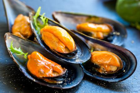 식욕을 돋우는 신선한 찐 바다 홍합의 매크로 닫습니다. 어두운 접시에 큰 파란색 홍합 스톡 콘텐츠