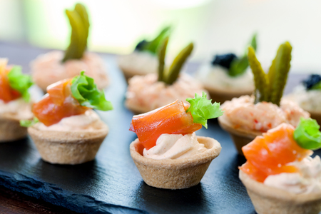 Macro close up of Mini puff pastry tartlets with smoked salmon,creamy crab and savory filling.