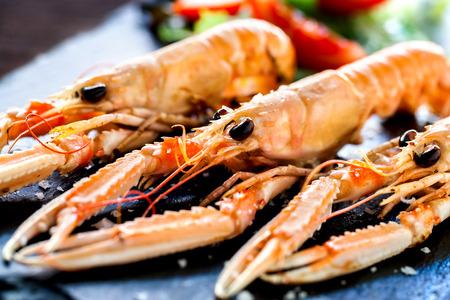 mariscos: Macro cerca de la parrilla gigante apetitoso plato de cangrejos de r�o con ensalada verde en el fondo.