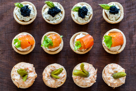 Close up Top view of variety of multiple mini puff pastry tartlets on wooden table. Open pastries filled with seafood.