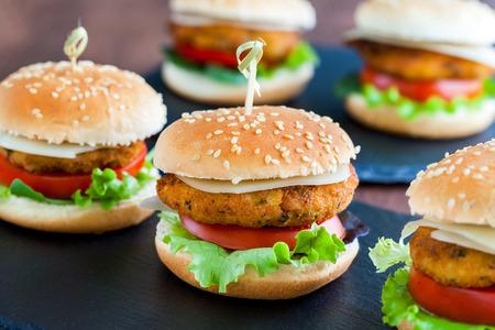 HAMBURGUESA: Extrema de cerca de varios mini hamburguesas de pollo apetitosas. Hamburguesas pequeños en fila para el servicio de catering.