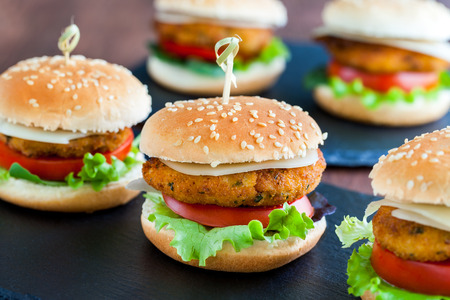 Extreme close up of multiple Appetizing mini chicken burgers. Small burgers in row for catering service. Archivio Fotografico