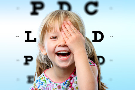 Close up face portrait of happy girl having fun at vision test.Conceptual image with girl closing one eye with hand and block letter eye chart in background. Stockfoto