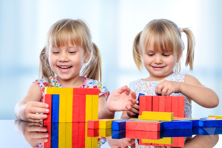 Close up portrait of two little girls playing with colorful wooden pieces at table.