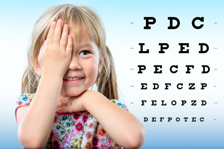 Close up portrait of cute little infant reviewing eyesight on chart. Girl closing one eye with hand reading vision chart.