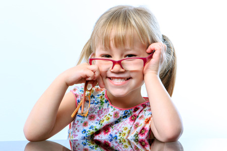 examen de la vista: Close up portrait of Funny little girl wearing eyewear on nose.