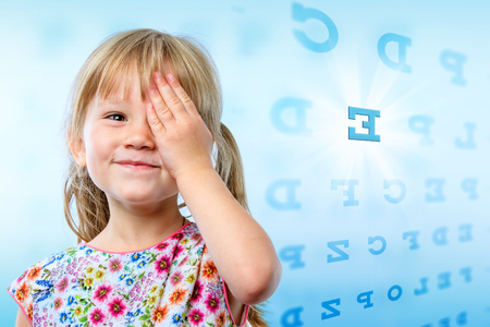 Close up portrait of little girl reading eye chart. Young kid testing one eye on block letter vision chart. Zdjęcie Seryjne - 47634723