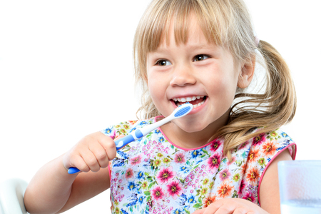 Close up portrait of cute five year old brushing teeth.Isolated on white background.