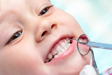 Macro dichte omhooggaand van weinig oude levensjaar tonende tanden bij tandcontrole omhoog. Tentisthanden die mondspiegel en houthakkersbijl dichtbij tanden houden.