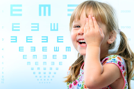 Close up fun portrait of little girl testing eye sight.Vision test chart in background.