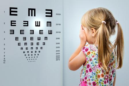 Close-up achteraanzicht van een meisje kijken naar oogtest chart.Kid sluit een oog met de hand.