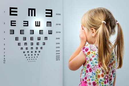 Close up rear view of little girl looking at eye test chart.Kid closing one eye with hand.
