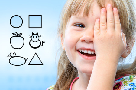 Close up face shot of little girl closing one eye with hand. Childish symbols in background as vision test chart. Banque d'images