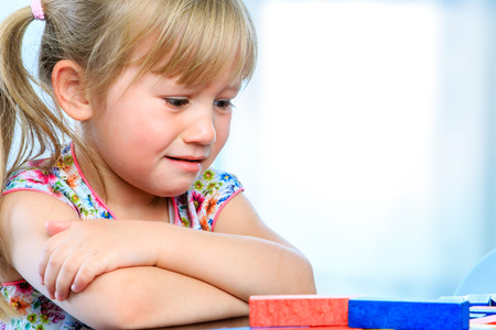 Close up portrait of unhappy little girl at table with educational game. Infant showing miserable sad face expression. Stock Photo
