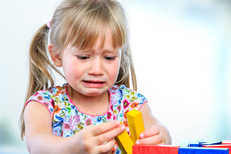 Close up portrait of crying little girl playing with wooden blocks at table.Frustrated girl showing moody behavior and long face. Foto de archivo