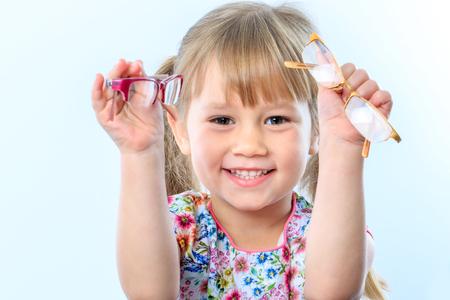 目のテストで 2 つのメガネを保持している幼児の肖像画を間近します。 写真素材