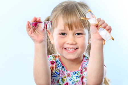 myopia: Close up portrait of infant holding two glasses at eye test.