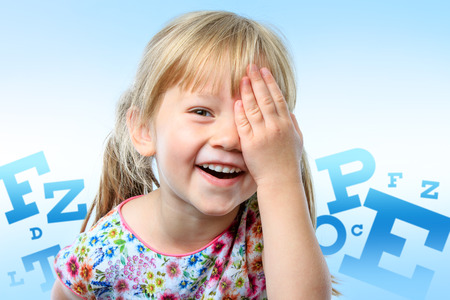 Close up fun portrait of little girl closing on eye with hand.Big block letter conceptual eye chart in background.